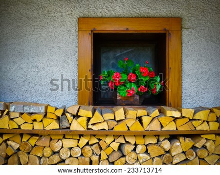 Chopped and stacked wood under a cottage window in Sauris, Carnia, Friuli, Italy, Europe - stock photo