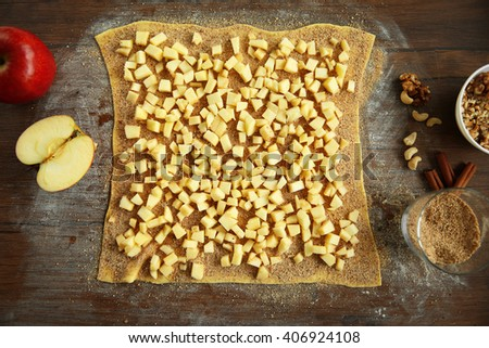 Chopped apples and dough on kitchen table - stock photo