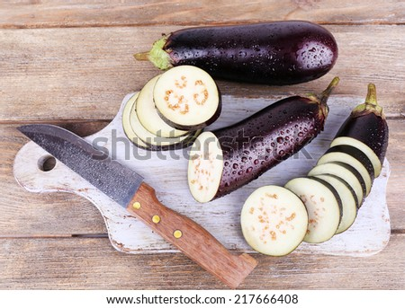 Chopped aubergines and knife on cutting board on wooden background - stock photo
