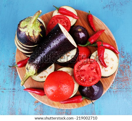 Chopped aubergines with tomatoes and chilly pepper on cutting board on wooden background - stock photo
