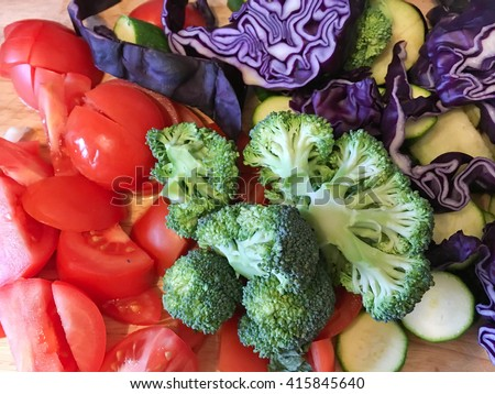 Chopped broccoli,tomatoes and purple cabbage on a  wooden baord