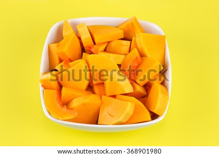 chopped butternut squash in the bow on yellow background