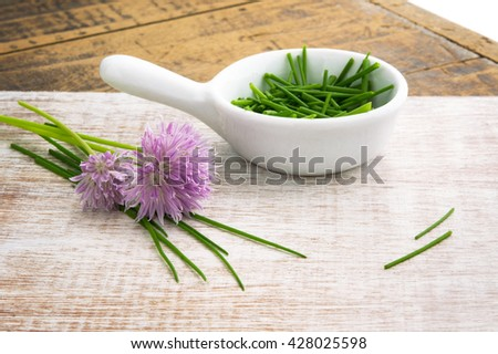 chopped chives with flowers window lit for soft focus on wood grain - stock photo