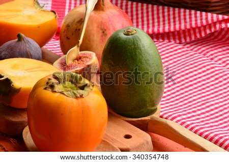 Chopped fig and persimmon on chopping board - stock photo