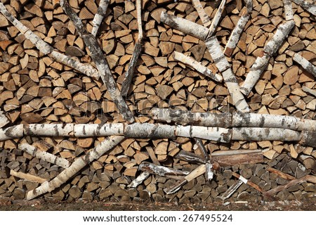 Chopped firewood stacked in a flat wall - stock photo