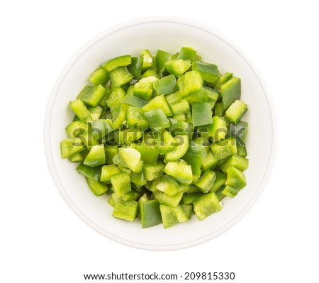 Chopped green capsicums in white bowls over white background  - stock photo