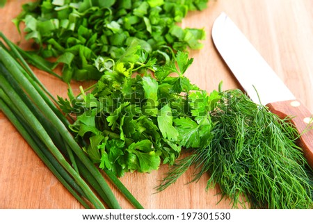 Chopped greens with knife on cutting board - stock photo