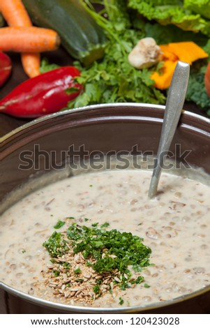 Chopped herbs and garlic being added to a large pot of creamy vegetable soup being prepared in the kitchen - stock photo