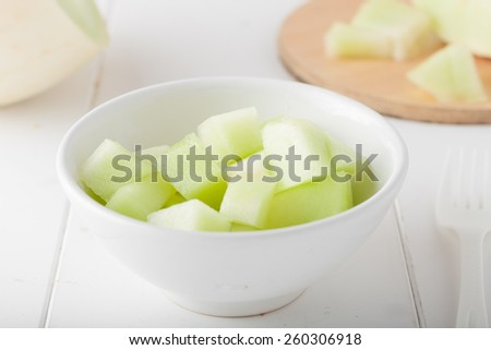 chopped honeydew melon in a white bowl - stock photo