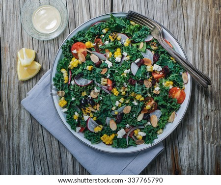 Chopped kale, grilled corn, tomatoes, dried cranberries and nuts salad on wood background - stock photo