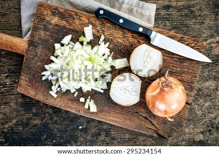 chopped onions on wooden cutting board, top view - stock photo