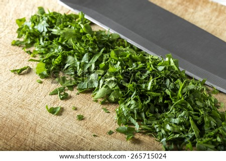 Chopped parsley leaf with a knife on a wooden table - stock photo