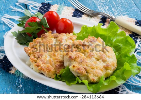 Chopped pork cutlets / Chopped pork cutlets with lettuce, cherry tomatoes and parsley on a plate, cloth napkin, fork on a blue wooden background. Selective focus - stock photo
