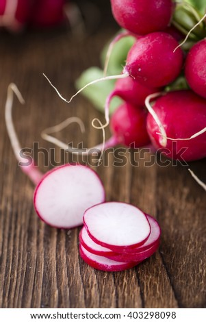 Chopped Radishes (close-up shot) on an old wooden table (selective focus) - stock photo