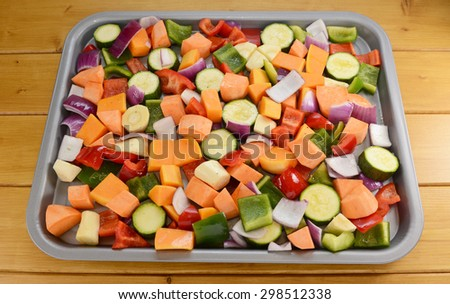 Chopped raw vegetables seasoned and drizzled with oil in preparation for roasting-  red pepper, parsnip, sweet potato, courgette, red onion, butternut squash, green pepper  - stock photo