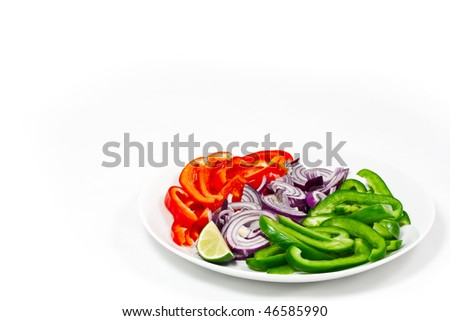Chopped red and green peppers on a white plate with a chopped red onion. Isolated on a white background, with lots of copyspace.
