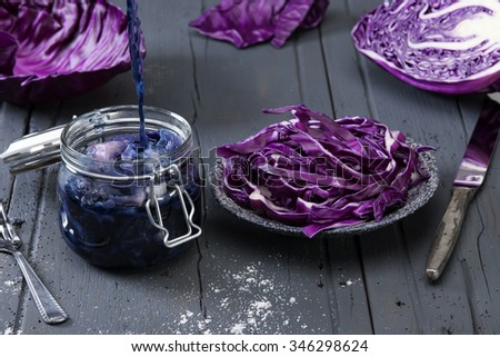 chopped red cabbage on old wooden table with preserving jar and boiled red cabbage
