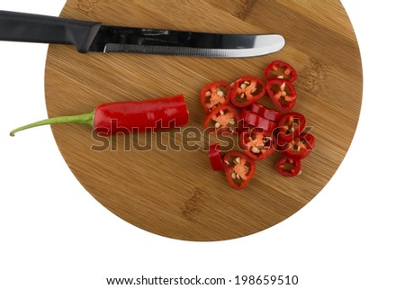 Chopped red chili peppers on wooden plate with knife isolated on white background