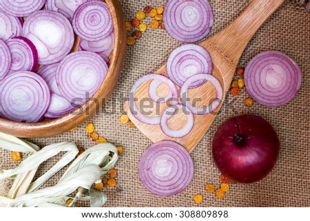 chopped red onions in wooden spoon  on sackcloth, as background - stock photo