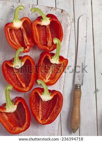 Chopped red peppers and knife on a chopping board - stock photo