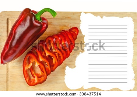 chopped rings and a whole red pepper on a board - stock photo