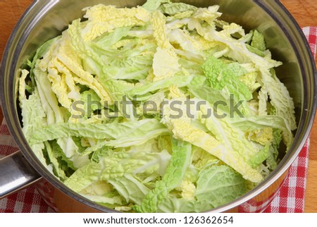Chopped savoy cabbage in stainless steel saucepan. - stock photo