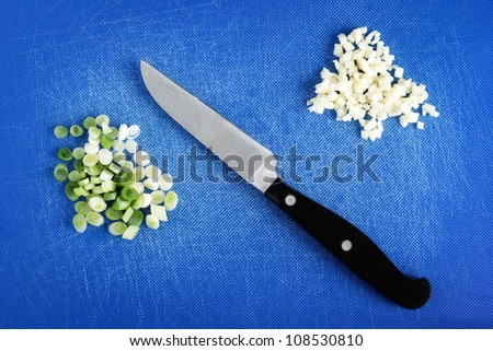 Chopped Spring Onions and Garlic on a blue Board.