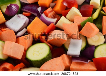 Chopped vegetables as an abstract background - red onion, sweet potato, courgette, green pepper, red pepper, parsnip and butternut squash - stock photo