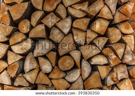 chopped wood stacked in a pile, harvesting of firewood for the stove, woodpile stacked behind the house - stock photo