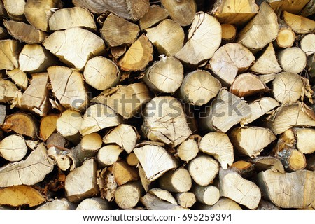 Chopped wood, stacked in a woodpile. Solid ecological fuel for heating the house in winter frost. Renewable energy.