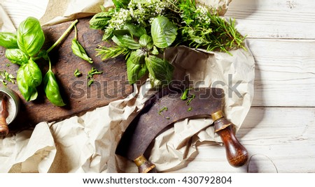 Chopping assorted fresh herbs with a mezzaluna knife on an old wooden chopping board on crumpled paper, overhead view - stock photo