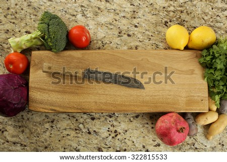 Chopping block surrounded by fruits and vegetables.