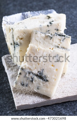 Chopping blue cheese roquefort on stone background, close up