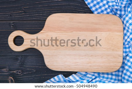 chopping board and towel on a dark wooden background