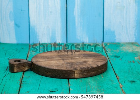 Chopping board for product montage on color wooden background