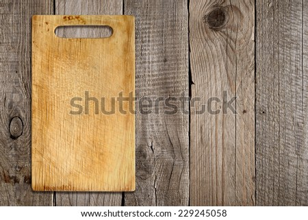 Chopping board on old wooden background - stock photo