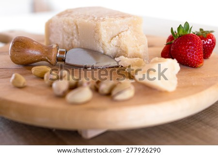 Chopping board with cheese, pistachios and strawberries. - stock photo