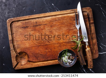 Chopping cutting board, seasonings and rosemary with fork and knife carving set on dark marble background - stock photo
