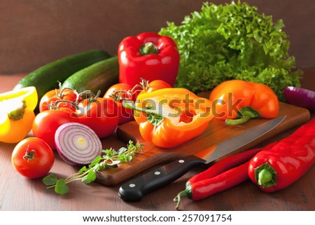 chopping healthy vegetables pepper tomato salad onion chilli on rustic background - stock photo