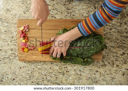 Chopping rainbow swiss chard in a modern kitchen - stock photo