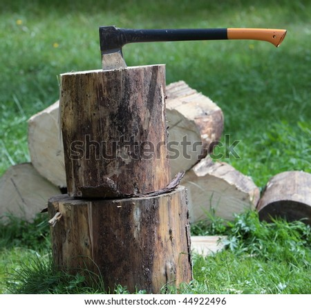 Chopping wood - ax in a log outdoors - stock photo