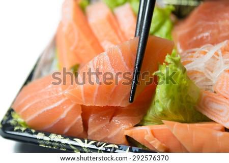 Chopstick grab a slice of Salmon Sashimi Japanese food   closeup isolated on white background - stock photo