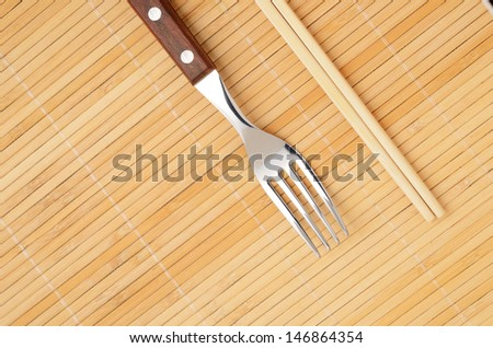 Chopsticks and a fork on the mat. Choice concept - stock photo
