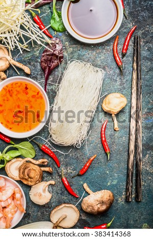 Chopsticks and Asian cooking ingredients and sauces on rustic background, top view. Chinese or Thai food concept - stock photo