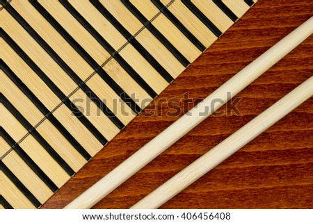 Chopsticks and bamboo mat over wooden background - stock photo