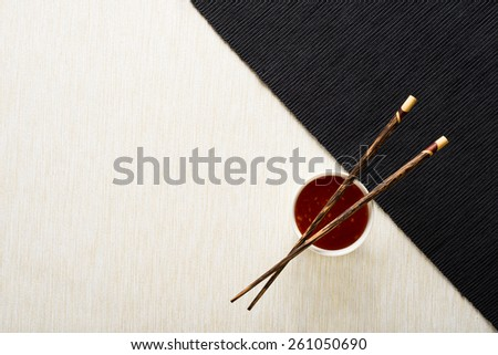 Chopsticks and bowl with sauce on table mat top view - stock photo