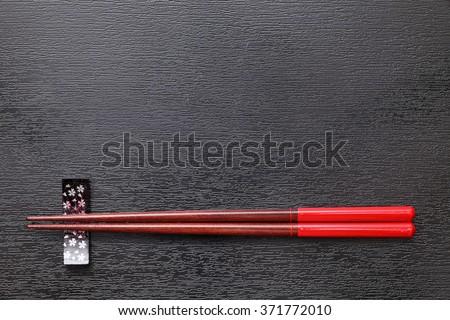Chopsticks and chopsticks rest on black tray background  - stock photo