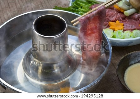 Chopsticks lifting up a thinly shaved slice of meat. - stock photo