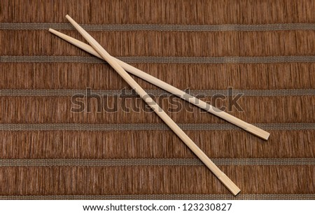 Chopsticks on brown bamboo background