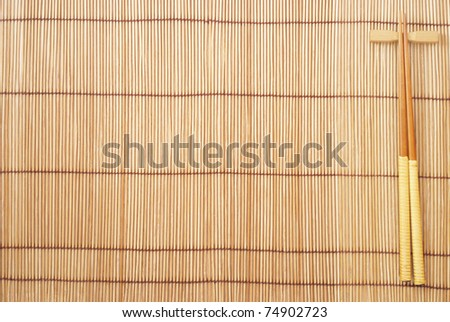Chopsticks on brown bamboo matting background - stock photo